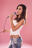 Singing woman. Portrait of a charming and beautiful woman singing with microphone in studio over pink background Royalty Free Stock Photos