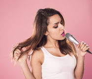 Singing woman. Portrait of a charming and beautiful woman singing with microphone in studio over pink background Stock Photos