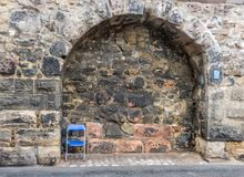 Single abandoned seat. A small blue chair alone in a recess of a city wall Royalty Free Stock Photos