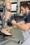 Single adult working on prosthetic leg adjustment. Single adult technician using tool to adjust length and stability on prosthetic leg assembly in workshop Stock Photos