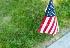 A single American flag placed at a veteran`s gravesite marker royalty free stock photography
