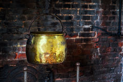 Single Antique vintage 1590 cauldron hand forged cooking pot hangged by the hearth fireplace old golden Stock Image