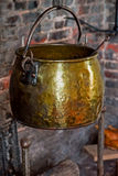 Single Antique vintage 1590 cauldron hand forged cooking pot hangged by the hearth fireplace old golden Stock Photo
