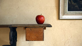 Single Apple On Antique Table. Single red apple sitting on the end of an antique table (partially shown) in a home setting.  Corner of a wall portrait is seen on Stock Image