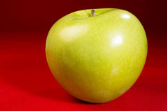 Single apple. Single green apple on red table royalty free stock images