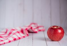 A single apple on a whitewashed wood top with a vintage red check dish towel. stock photo