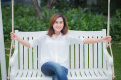 Single asian women adult relax sitting at swing bench in the park. Royalty Free Stock Photo