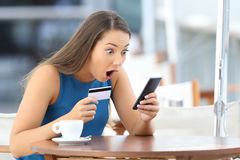 Astonished buyer finding offer on line in a bar. Single astonished buyer holding phone and credit card finding a good offer on line sitting in a restaurant stock photos