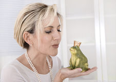 Single attractive older woman with a frog king in her hands. Single attractive maturer woman kissing a frog king in her hands stock image