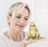 Single attractive older woman with a frog king in her hands. Stock Photos