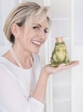 Single attractive older woman with a frog king in her hands. Single attractive maturer woman kissing a frog king in her hands stock photo
