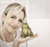 Single attractive older woman with a frog king in her hands. Single attractive maturer woman kissing a frog king in her hands stock photos