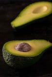 Single avocado severed in half on dark tray Royalty Free Stock Photos