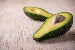 Single avocado severed in half on white worn wooden board Stock Photo