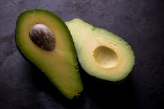Single avocado severed in half on worn black tray Stock Photography