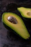 Single avocado severed in half on worn dark tray Stock Photography