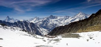 Single backcountry skier in a vast mountain landscape on his way down from a high summit with a great view of the Matterhorn and s Stock Photo