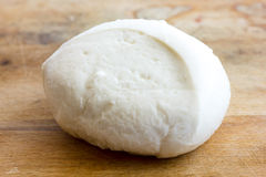 Single ball of mozzarella cheese on rustic wood surface. Stock Images