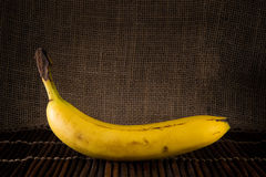 A single banana. A single yellow ripe banana with a burlap background and sitting on a wooden placemat Stock Image