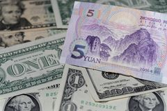 Banknote of five Chinese yuan against background of american dollars. Single banknote of five Chinese yuan against background of american dollars stock photography