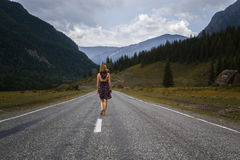 Single barefoot woman is walking along the mountain road. Travel, tourism and people concept Royalty Free Stock Image
