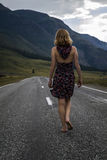 Single barefoot woman is walking along the mountain road. Travel, tourism and people concept Stock Photo