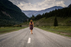 Single barefoot woman is walking along the mountain road. Travel, tourism and people concept Stock Photos