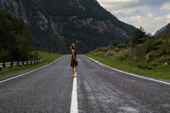 Single barefoot woman is walking along the mountain road. Travel, tourism and people concept Stock Image