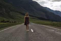 Single barefoot woman is walking along the mountain road. Travel, tourism and people concept Royalty Free Stock Photos