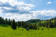 Single barn in the middle of a meadow on a medium clouded day royalty free stock photo