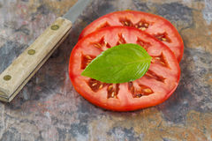 Single basil leaf and sliced tomato with knife on real stone boa Royalty Free Stock Images
