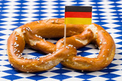 Single Bavarian pretzel with german flag. On blue and white rhombus napkin Royalty Free Stock Images