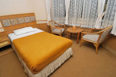 Single bed in modern hotel room with chairs Royalty Free Stock Photography