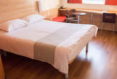Single bed in modern hotel room with chairs Stock Photography