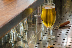 Single beer glass and bottle opener behind the bar counter Royalty Free Stock Images