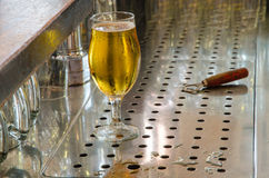 Single beer glass and bottle opener behind the bar counter stock image