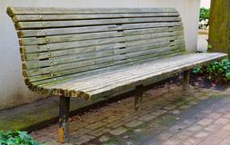 Single Bench perspective. City Park Bench perspective against tan building wall Stock Photos