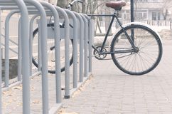 Single bicycle chained up at the bicycle rack stock photography