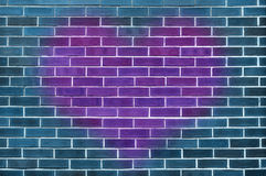 Single big purple heart on a blue brick wall Stock Photo