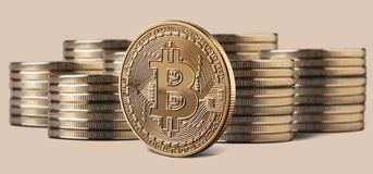 Single bitcoin coin standing in front of stacks of coins. Single bitcoin coin or icon standing in front of stacks of coins on a beige background. Cryptocurrency royalty free stock images