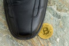 Single Bitcoin under a black leather shoe Stock Images
