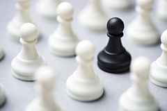 Single black chess piece amongst white ones. Single black pawn chess piece amongst multiple white ones on a grey background with focus to the black one in a Stock Image