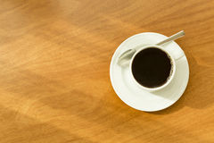 Single black cup of hot coffee in a white mug on a white saucer with a silver spoon on a wooden table in sunlight Royalty Free Stock Photo