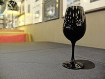 Single Black Glass of Wine at The Right Corner with Blur Background Stock Photo