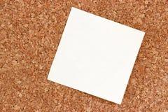 Sticky note on a cork pinboard. A single blank sticky note hanging on a cork pinboard stock photography
