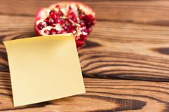 Single blank yellow square paper sticky sticker before one half of red ripe fresh pomegranate. On old brown weathered rustic planks stock photo