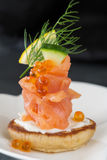 Single Blini appetiser with smoked salmon, caviar and sour cream Stock Photo