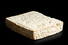 Single block of lightly smoked tofu. Single block of lightly smoked tofu isolated on black Royalty Free Stock Photo