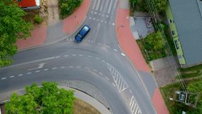 Single blue car is driving across curved intersection in city, aerial view.  stock video footage