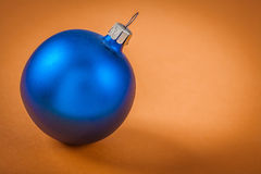 Single blue christmas ball on light brown background Royalty Free Stock Images